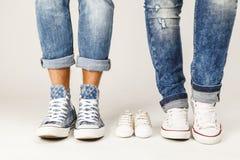 Pies de los padres y zapatos de bebé Fotografía de archivo