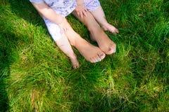 Pies de madre cariñosa feliz y su niño al aire libre Imagen de archivo libre de regalías