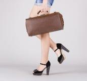 Pies de muchacha con una maleta a disposición. Imágenes de archivo libres de regalías