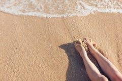 Pies de muchacha en la arena en la playa cerca del agua Fotos de archivo libres de regalías