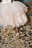 Pies de muchacha en los zapatos blancos y confeti en el piso Fotos de archivo libres de regalías