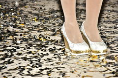 Pies de muchacha en los zapatos y las medias blancos y confeti en el piso Fotografía de archivo libre de regalías