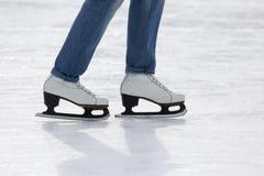Pies de muchacha patinadora que patina en pista de hielo Imágenes de archivo libres de regalías