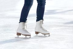 Pies de muchacha patinadora que patina en pista de hielo Imagen de archivo libre de regalías