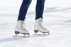 Pies de muchacha patinadora que patina en pista de hielo Fotos de archivo