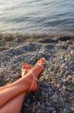 Pies de muchacha que toma el sol en una playa pedregosa - vacaciones y concepto del viaje Imagen de archivo libre de regalías