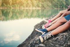 Pies de niños que se sientan en la roca en naturaleza Imagen de archivo