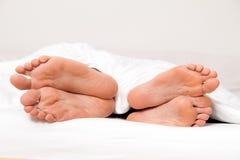 Pies de pares en cama. Separación y divorcio Fotos de archivo libres de regalías