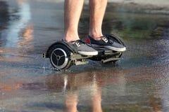 Pies de paseo de un hombre en un segway en el asfalto mojado imagenes de archivo