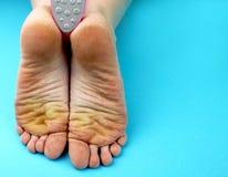 Pies de pie de la limpieza con una sierra o un cepillo Limpieza de los pies del hongo foto de archivo libre de regalías
