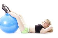 Pies de reclinación de la mujer en bola Fotografía de archivo libre de regalías