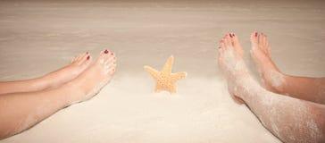 Pies de Sandy con las estrellas de mar Foto de archivo