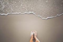 Pies de Sandy que se lavarán por una onda suave inminente del mar foto de archivo