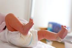 Pies de segundos y de minutos recién nacidos del niño del bebé después del nacimiento que miente en la toalla foto de archivo libre de regalías