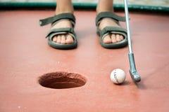 Pies de un niño que juega a mini golf Foto de archivo libre de regalías