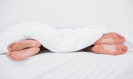 Pies de un par en sus lados opuestos en cama Imágenes de archivo libres de regalías