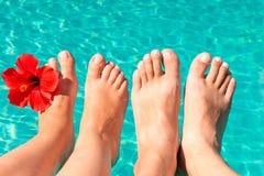 Pies de un par joven por la piscina Fotos de archivo