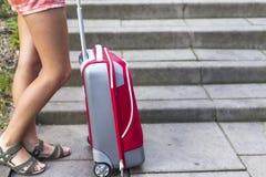 Pies de una chica joven cerca de la maleta roja Imagen de archivo