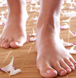 Pies de una hembra joven en una alfombra de bambú foto de archivo libre de regalías