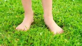 Pies de una muchacha de diez años en la hierba verde foto de archivo