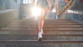 Pies de una muchacha hermosa joven Ella va encima de las escaleras 4k metrajes