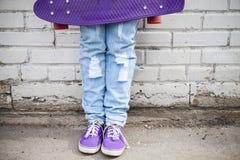 Pies del adolescente en tejanos con el monopatín Foto de archivo libre de regalías
