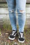 Pies del adolescente en vaqueros y zapatillas de deporte negras Imagenes de archivo