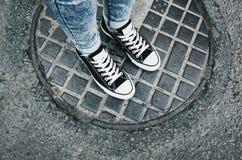 Pies del adolescente en zapatillas de deporte gumshoes Foto de archivo