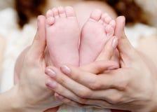 Pies del bebé ahuecados en las manos de las madres Imagen de archivo libre de regalías
