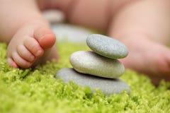 Pies del bebé al lado de la pila de piedras del zen Imágenes de archivo libres de regalías