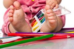 Pies del bebé con la pintura y los lápices Imágenes de archivo libres de regalías