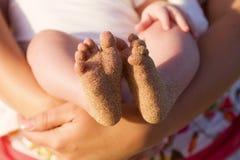 Pies del bebé cubiertos en arena de la playa Imagen de archivo libre de regalías