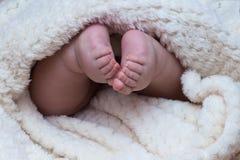 Pies del bebé debajo de la manta Imagenes de archivo