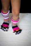 Pies del bebé en calcetines multicolores calientes, largos con los dedos del pie Fotografía de archivo
