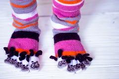 Pies del bebé en calcetines multicolores calientes, largos con los dedos del pie Fotografía de archivo libre de regalías