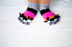 Pies del bebé en calcetines multicolores calientes, largos con los dedos del pie Foto de archivo