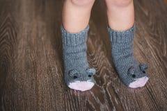 Pies del bebé en calcetines del ratón del invierno en el piso de madera Fotografía de archivo
