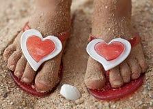 Pies del bebé en deslizadores de la playa Fotos de archivo libres de regalías