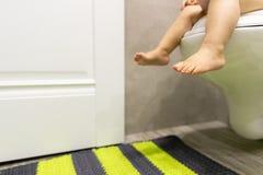 Pies del bebé en el retrete Concepto del ` s de los niños restroom foto de archivo