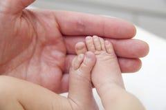Pies del bebé en la mano del padre Imágenes de archivo libres de regalías