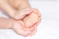 Pies del bebé en las manos de la madre Fotografía de archivo libre de regalías