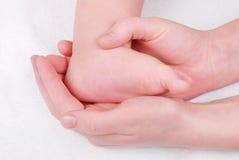 Pies del bebé en las manos de la mama Foto de archivo
