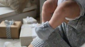 Pies del bebé en los zapatos hechos punto que se sientan en los brazos almacen de video