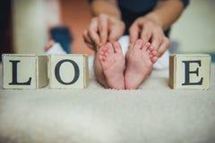 Pies del bebé en manos de la madre ` Recién nacido minúsculo s en el primer en forma de corazón femenino Foto de archivo libre de regalías