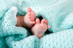 Pies del bebé en manta Imagen de archivo libre de regalías