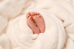 Pies del bebé en manta fotografía de archivo