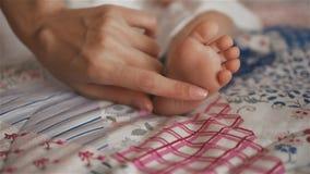 Pies del bebé en primer de la mano de la madre en casa Pierna de la mamá y del niño metrajes