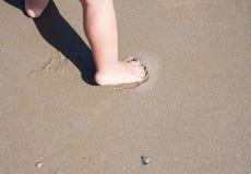 Pies del bebé que caminan en la playa Italia de la arena Imagenes de archivo