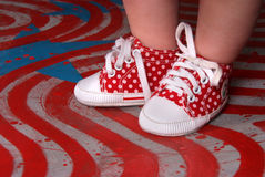 Pies del bebé que llevan los zapatos rojos Imagen de archivo libre de regalías