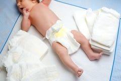 Pies del bebé recién nacido en la tabla cambiante con los pañales Niña o muchacho linda dos semanas de viejo Cuerpo seco y sano y foto de archivo